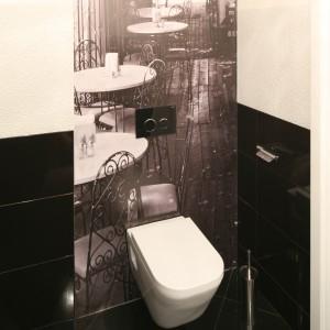 W toalecie dla gości okładzinę ściana tworzy kompozycja białych i czarnych płytek, a uzupełnia równie elegancka fototapeta. Wykonane w sepii zdjęcie prezentuje ogródek miejskiej kawiarenki i wprowadza do łazienki klimat retro. Projekt: Karolina i Artur Urban. Fot. Bartosz Jarosz.