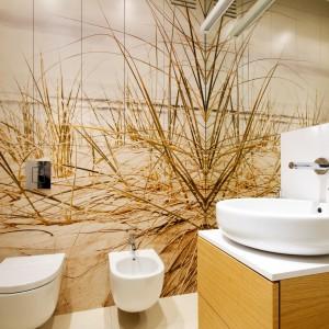 Każdy element wystroju łazienki kojarzy się nieodłącznie z plażą. Grafika z motywem nadmorskich wydm i roślin pozwala przenieś się myślami się na słoneczny, muskany falami brzeg. Projekt: Monika i Adam Bronikowscy. Fot. Monika i Adam Bronikowscy.