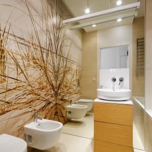 Lustro umieszczone na ścianie z umywalką doskonale powiększa całe wnętrze, a grafika na całą ścianę wypełnia łazienkę kolorem piasku i szumem wody. Projekt: Monika i Adam Bronikowscy. Fot. Monika i Adam Bronikowscy.