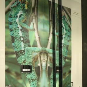 Ponieważ na ścianie prostopadłej do tej z fototapetą umieszczone zostało ogromne lustro, wydaje się, że kameleonów jest tutaj więcej niż jeden... Projekt: Katarzyna Mikulska-Sękalska. Fot. Bartosz Jarosz.