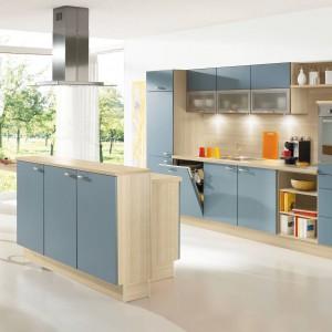 Połączenie beżowej bazy z drewnianym dekorem i niebieskich, lekko przydymionych, matowych frontów. Współczesna kuchnia z domowym, przytulnym klimatem. Fot. Pino, program PN140.