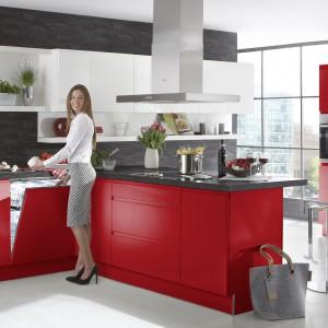 Czerwone fronty i korpusy mebli kuchennych zwieńczono ciemnoszarym blatem. Kombinacja dwóch wyrazistych barw stworzyła elegancką kompozycję. Całość utrzymano w nowoczesnym stylu: gładkie fronty i brak uchwytów. Fot. Nolte Kuechen, kolekcja Alpha Lack.