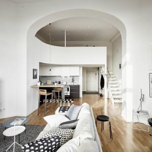 Mieszkanie zlokalizowano w budynku, który został wybudowany na początku XX wieku, zastępując istniejącą tu wcześniej zbrojownię. Lokalizacja wpłynęła na charakter wnętrza, kształt pomieszczeń i ich wysokość. Wysokie, duże wnęki zastępujące drzwi pomiędzy pomieszczeniami prezentują się niezwykle efektywnie i pełnią same w sobie rolę dekoracji. Fot. Stadshem.