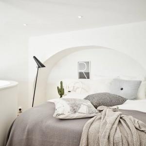 Na półpiętrze zlokalizowano jasną, przytulną sypialnię. Oszczędne dekoracje rekompensują przytulne i wzorzyste tkaniny oraz fantazyjne półkola nad łóżkiem, zastępujące wizualnie zagłówek. Fot. Stadshem.