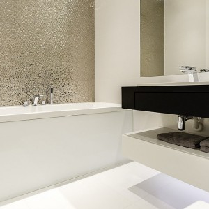 W łazience dla pań ścianę nad wanną wykończono piękną, srebrną mozaiką. Nadaje ona wnętrzu elegancji i przeistacza zwykłą łazienkę w luksusowy salon kąpielowy. Projekt: Anna Maria Sokołowska i Marta Piątkowska. Fot. foto & mohito.