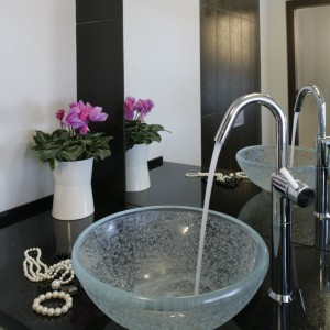 Ustawiona na granitowym blacie subtelna szklana umywalka świetnie zdobi łazienkę i stanowi wyraźny akcent stylu glamour. Fot. Monika Filipiuk-Obałek.