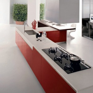 Pomysł na długą wyspę z czerwonymi, lakierowanymi frontami. Propozycja wyłącznie do dużej kuchni. Fot. Demirbag.