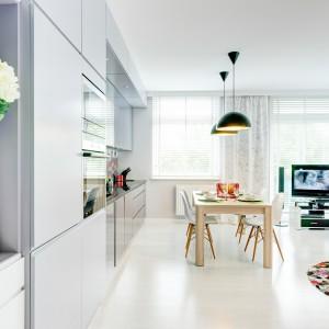 Umowną granicę pomiędzy salonem i kuchnią wyznacza stół jadalniany. Z jasną aranżacją wnętrza kontrastują wiszące nad stołem czarne, loftowe lampy. Projekt: Saje Architekci. Fot. foto&mohito.