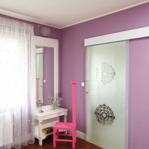 W sypialni wydzielono miejsce na toaletkę. Rama lustra została pomalowana na perłowy odcień. Identyczny kolor ma tło tapety  umieszczonej na ścianie za łóżkiem. Fot. Bartosz Jarosz.