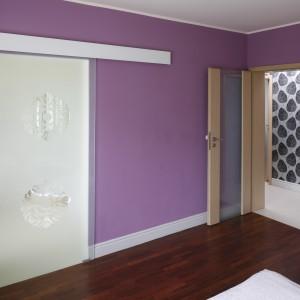 Na szklanych drzwiach przesuwnych powtórzono motyw znajdujący się na tapecie. Dekoracyjne drzwi prowadzą do prywatnej łazienki. Fot. Bartosz Jarosz.