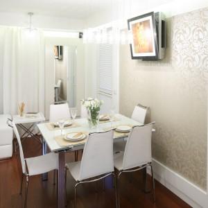 Piękna jadalnia zlokalizowana w salonie. Ścianę za jadalnią pokryto subtelną, beżową tapetą z delikatnym wzorem. Stół i krzesła utrzymane w jasnej kolorystyce, dominującej w całym pomieszczeniu. Projekt: Małgorzata Mazur. Fot. Bartosz Jarosz.