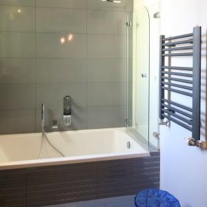 Bardzo mała łazienka jest elegancka i praktyczna. Parawan nawannowy składa się z dwóch szklanych tafli łączonych na zawiasach. Projekt: Arkadiusz Grzędzicki. Fot. Bartosz Jarosz.