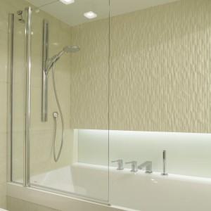 Szklana tafla parawanu pozwala w pełni docenić piękna, trójwymiarową powierzchnię płytek ceramicznych, którymi wykończono ścianę nad wanną. Projekt: Małgorzata Borzyszkowska. Fot. Bartosz Jarosz.