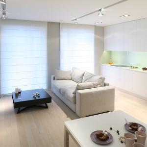 Połączony z kuchnią salon urządzono w minimalistycznym stylu. Stojąca po środku pomieszczenia sofa to właściwie jedyny element jego wystroju. Poza funkcją wypoczynkową wyznacza ona symboliczna granice między obiema strefami. Projekt: Monika i Adam Bronikowscy. Fot. Bartosz Jarosz.