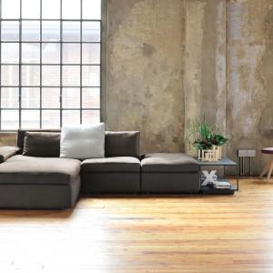 Szary narożnik modułowy z oferty marki Grafo z obszernymi siedziskami oraz zintegrowanymi stolikami pomocniczymi. Fot. House&more.pl