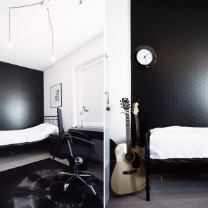Monochromatyczny czarno-biały pokój robi piorunujące wrażenie. Wyraziście czarna ściana za prostym łóżkiem kontrastuje z otaczającą ją bielą. Projekt i Fot. Soma Architekci.