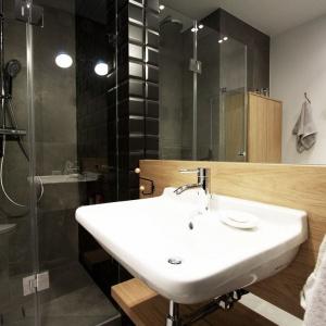Męska łazienka to pochwała surowości i praktyczności. Zamiast wanny zastaniemy tutaj kabinę prysznicową ze szklanymi, prostymi, minimalistycznymi drzwiczkami. Czernie i szarości przełamują drewniane akcenty. Projekt i Fot. Soma Architekci.