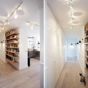 W jasnym przedpokoju zlokalizowano dużo praktycznych półek i schowków. Na ściance sąsiadującej z salonem urządzono podręczną biblioteczkę. Projekt i Fot. Soma Architekci.