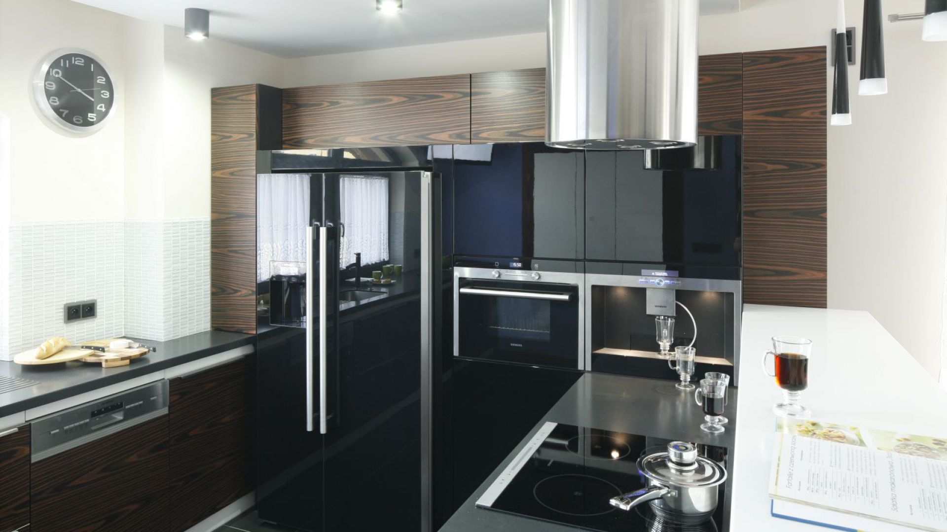 Czarne, połyskujące powierzchnie sprzętów kuchennych podkreślają nowoczesny charakter wnętrza. Projekt: Marta Kilan. Fot. Bartosz Jarosz.