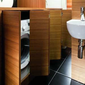 Mimo niewielkich rozmiarów toalety udało się tutaj zmieścić pralkę. Wysoka komoda wyposażona została w podwójne, składane harmonijkowo fronty. Dzięki temu drzwiczki można wygodnie otworzyć nawet w ciasnym pomieszczeniu. Projekt: Piotr Gierałtowski. Fot. Bartosz Jarosz.