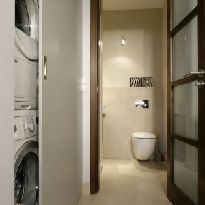 W korytarzu prowadzącym do łazienki zaplanowano zabudowę w postaci dużej szafy gospodarczej. Łatwy dostęp do umieszczonych w niej sprzętów AGD zapewniają przesuwane drzwi. Projekt: Iwona Cała. Fot. Monika Filipiuk-Obałek.
