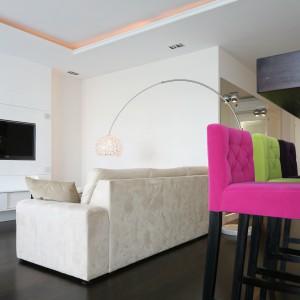 W zintegrowanej przestrzeni dziennej jasnobeżowa sofa odznacza się swą stonowaną kolorystyką, wyznaczając tym samym strefę wypoczynku. Zdobi ją kryształowa lampa oraz meble na wysoki połysk. Projekt: Agnieszka Żyła. Fot. Bartosz Jarosz.