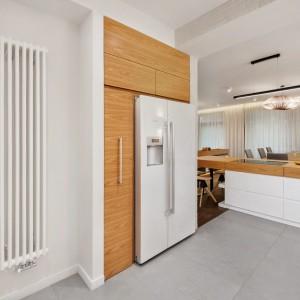 Pojemną lodówkę typu side by side zlokalizowano na zabudowie sciennej z drewnianych paneli. Projekt: Razoo Architekci. Fot. Meluzyna Studio.