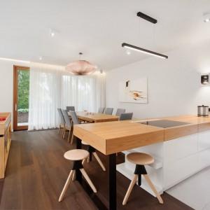 Kuchnię od jadalni oddziela półwysep, którego blat przechodzi w niewielki bar dla trzech osób. Przestrzeń półwyspu zagospodarowano jako strefę gotowania, z gładką płytą kuchenną, która niemal chowa się w drewnianym blacie. Projekt: Razoo Architekci. Fot. Meluzyna Studio.