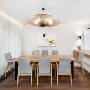 W rogu obszernej strefy dziennej zlokalizowano duży stół jadalniany na 8 osób. Jadalnia ma bezpośredni dostęp do dziennego światła, wpadającego do wnętrza przez wielkowymiarowe przeszklenia. Projekt: Razoo Architekci. Fot. Meluzyna Studio.