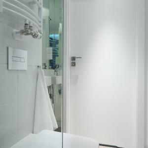 W małej łazience celowo unikano stosowania sztywnych podziałów przestrzeni, a wyposażenie ograniczono do niezbędnego minimum. Strefę prysznica od pozostałej części pomieszczenia oddziela jedynie wąska szklana ścianka w minimalistycznej formie: bez żadnych okuć. Fot. Bartosz Jarosz
