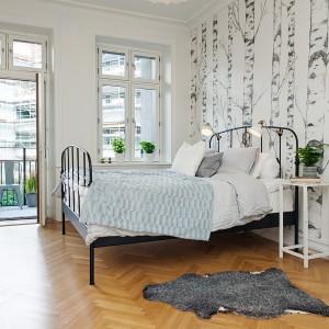 Tapeta z delikatnym, czarno-białym rysunkiem drzew doskonale wpisuje się w aranżację sypialni utrzymaną w skandynawskim stylu. Fot. Alvem Makleri.