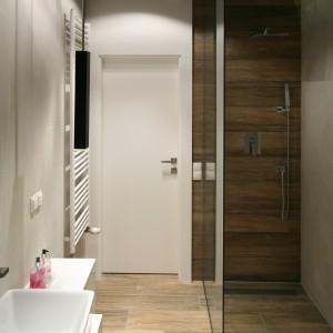 Podłogę oraz ścianę za prysznicem wykończono płytkami imitującymi deski. Prysznic typu walk-in oddzielony jest jedną szklaną ścianką, a w posadzce zainstalowano odpływ z pełnym rusztem. Projekt: Dominik Respondek. Fot. Bartosz Jarosz.