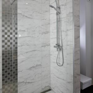 Prysznic ma ciekawą formę wnęki i umieszczony jest na niewielkim podwyższeniu. Odpływ umieszczony jest przy ścianie, co zapewnia  właściwy spadek wody. Projekt: Michał Wielecki, Łukasz Hoffman. Fot. Bartosz Jarosz.