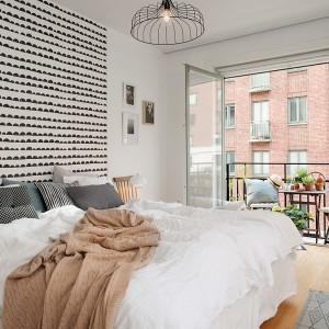 Tapeta w drobny, czarno-biały wzór umieszczona na fragmencie ściany za łóżkiem dodaje sypialni charakteru i przełamuje monotonną biel. Fot. Alvhem Makler.