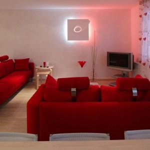 Meble wypoczynkowe w kolorze intensywnej czerwieni to jedyne elementy, poza telewizorem, wyposażenia pokoju dziennego. Projekt: Piotr Grzywacz. Fot. Tomasz Markowski.