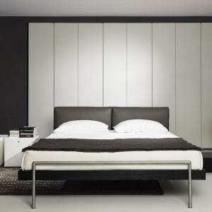Czarną ścianę połączono z białymi, prostymi elementami. Łóżko Shin projektu P. Lissoni. Fot. Porro.