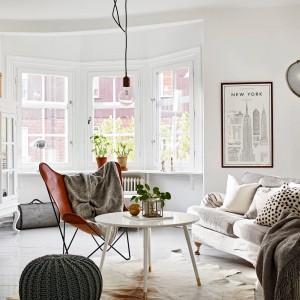 Wysoki sufit i wszechobecna biel nadają wnętrzu salonu wrażenia przestronności. Proste półki, lekki stoli kawowy i fotel na szczupłych nogach oraz oświetlenie pozbawione ozdobnych abażurów wpisują się w świeżą aranżację. Fot. Stadshem.
