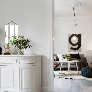 Funkcję toaletki w sąsiadującej z salonem sypialni pełni proste lustro, zawieszone na ścianie i piękna stylizowana komoda. Fot. Stadshem.
