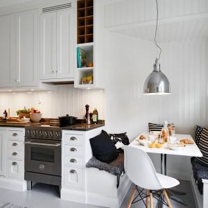 Ściany w kuchni wykończono pionową boazerią pomalowaną na biało. Buduje ona domowy, przytulny klimat, a biały kolor nie przytłacza wnętrza. Kamienny blat kuchenny w ciemnobrązowym kolorze estetycznie kontrastuje z otaczającą go bielą. Urokliwym i ciekawym akcentem jest wnęka, w którą wpasowano stolik z zabudową, tworzącą siedziska. Nad stolikiem zawisła industrialna, metalowa lampa. Fot. Stadshem.