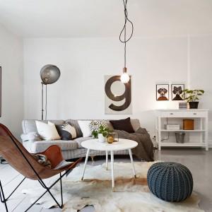 W jasnym salonie dominuej chłodna kolorystyka. Charakter pomieszczenia ocieplają tkaniny i meble: przytulna sofa ze stosem dekoracyjnych poduch, dywan z motywem zwierzęcym i wełniany, urokliwy puf. Fot. Stadshem.