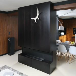 W niewielkim salonie, podporządkowanym funkcji wypoczynkowej, drewno stało się głównym motywem aranżacji przestrzeni. Podobnie jak w kuchni i jadalni zdobi ono całe ściany pomieszczenia. Projekt: Kasia Dudko, Michał Dudko. Fot. Bartosz Jarosz.