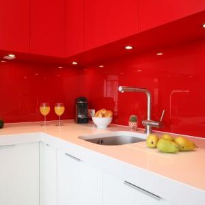 Biały blat, kontrastujący z intensywną czerwienią wiszących szafek i szkła na ścianie, oświetlają halogeny zainstalowane w spodach szafek. Projekt: Iza Szewc. Fot. Bartosz Jarosz.
