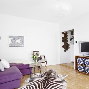 Dekoracyjnymi akcentami w salonie są fioletowa, przyciągająca wzrok kanapa, dywan z motywem zwierzęcym oraz urokliwe niebiesko-białe, plecione kosze na szafce RTV. Powiem elegancji zapewnia stylizowane barokowe krzesło. Fot. Vastanhem.
