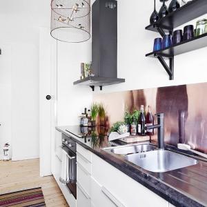 Ścianę nad blatem kuchennym, zamiast popularnymi kaflami, pokryto metalowym panelem. Leko miedziany kolor powierzchni, w połączeniu z nowoczesną baterią i stalowym okapem, wprowadzają do wnętrza element industrialnej stylistyki. Fot. Vastanhem.