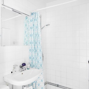 Ściany i podłogę w łazience pokrywają białe płytki. Towarzyszą im biała ceramika sanitarna oraz proste, bezramowe lustro. Z prostymi formami i jasną kolorystyką idealnie komponuje się wzorzysta zasłona prysznicowa, z motywem w kolorze lodowatego błękitu. Razem z dominującą bielą, tworzą świeże, orzeźwiające wnętrze. Fot. Vastanhem.