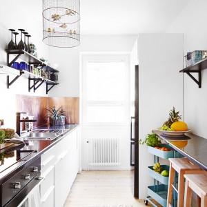 Ciemny blat kuchenny efektownie kontrastuje z białymi meblami. Kuchnię ozdabia bogactwo dodatków, nadających jej domowego, prowansalskiego klimatu. Klatka dla ptaków jako dekoracja to oryginalny akcent. Fot. Vastanhem.