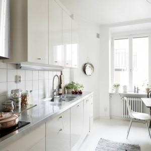 Ściany i podłoga w kuchni zostały pomalowane na biało. Połyskujące, gładkie fronty mebli mają delikatny odcień kremowy, dzięki czemu dyskretnie ocieplają chłodną aranżację wnętrza, w której stalowy blat kuchenny i białe ściany buduja chłodny klimat. Fot. Stadshem.