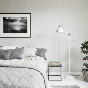 Szare ściany w sypiani kolorystycznie pięknie komponują się z poduszkami dekoracyjnymi na łóżku i plecionym koszyczkiem, w którym ustawiono donicę. Fot. Stadshem.