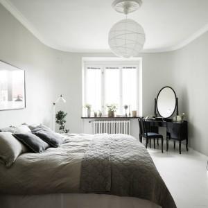 Piękna szara sypialnia urzeka elegancją i przytulnym charakterem. Jej ściany pokryto ciepłym odcieniem szarości. Kształt bryły budynku definiuje formę pomieszczenia, które jest delikatnie zaokrąglone i – dzięki temu – wygląda oryginalnie i efektownie. Fot. Stadshem.
