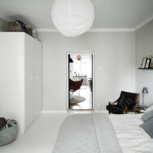 Dominujące w sypialni szarości przełamano czystą bielą. Biała są belki, położone na podłodze, sztukaterie pod sufitem, szafa oraz abażur do żyrandola.  Fot. Stadshem.